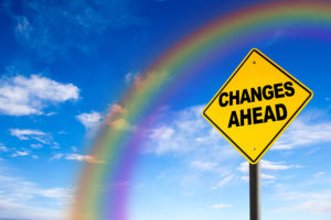 Changes Ahead sign against a blue sky with rainbow. Concept of situation change for the better.